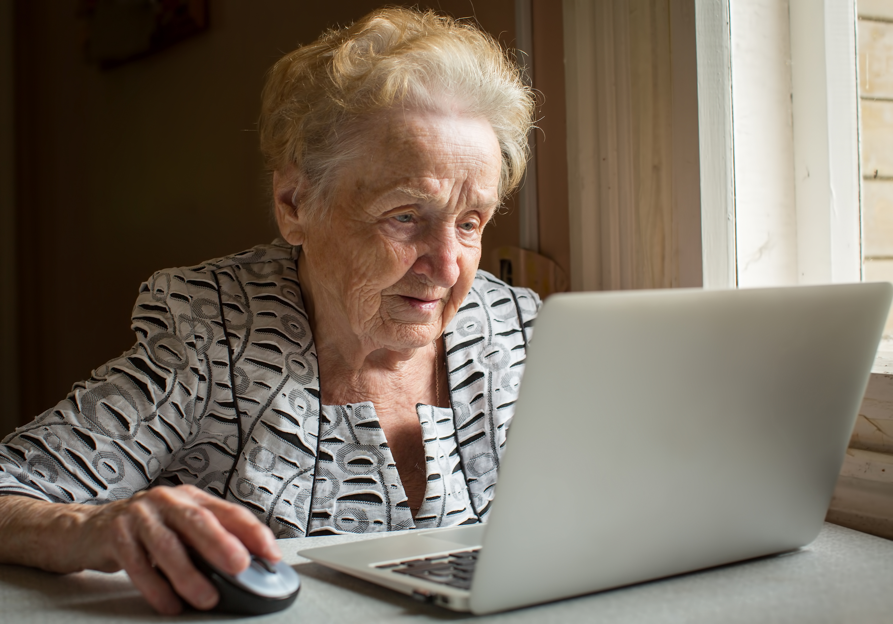 Elderly woman sitting at the table and types on laptop.